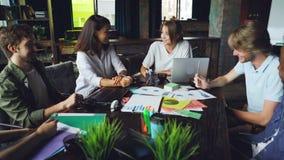 快乐的工友多种族队是谈和笑一起坐在桌上在会议期间在现代顶楼 影视素材