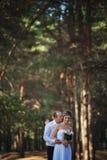 快乐的已婚夫妇亲吻在森林里 免版税库存图片