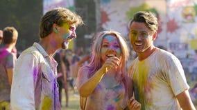快乐的年轻人和妇女获得乐趣在音乐会,朋友上色与粉末 影视素材