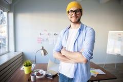快乐的年轻人在一个时髦办公室便服商人戴着眼镜和站立 免版税库存图片