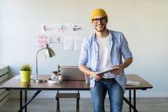快乐的年轻人在一个时髦办公室便服商人戴着眼镜和站立 免版税库存照片