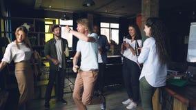 快乐的年轻人跳舞和有乐趣的慢动作与他的工友的在与饮料和音乐的办公室聚会 愉快 股票录像