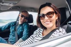 快乐的年轻传统夫妇有一次长的自动旅途 安全骑马汽车概念广角在汽车视图图象里面 免版税库存图片