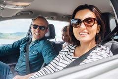 快乐的年轻传统家庭有一次长的自动旅途和一起微笑 安全骑马在广角的汽车里面的汽车概念 免版税库存照片