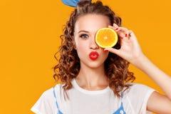 快乐的年轻卷曲妇女女孩用在黄色背景的桔子 免版税库存照片