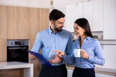 快乐的年轻同事谈话在厨房里 免版税库存图片