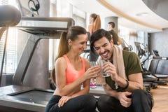 快乐的年轻喝简单的水的人和妇女在断裂期间在健身 库存图片