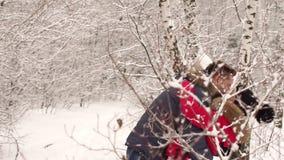 快乐的年轻夫妇在雪落在森林里 股票录像