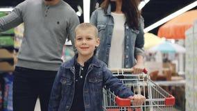 快乐的年轻家庭妈妈、爸爸和小男孩在有看购物的台车的大型超级市场一起走  股票录像