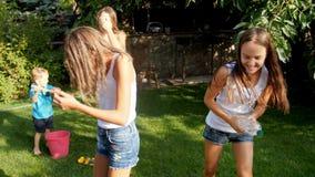快乐的年轻家庭慢动作录影有使用与水枪和水水管的孩子的在庭院里在热的夏天 影视素材