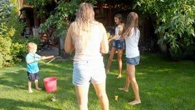 快乐的年轻家庭慢动作录影有使用与水枪和水水管的孩子的在庭院里在热的夏天 股票录像
