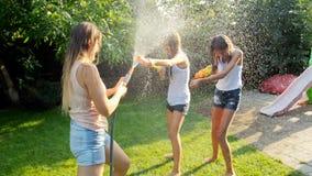 快乐的年轻家庭慢动作录影有使用与水枪和水水管的孩子的在庭院里在热的夏天 股票视频
