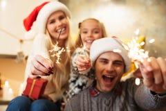 快乐的年轻家庭特写镜头照片与儿童藏品闪闪发光的 图库摄影