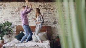 快乐的年轻恋人在粗心大意地笑的床上在家跳舞获得乐趣在卧室和 愉快的人民,现代 影视素材