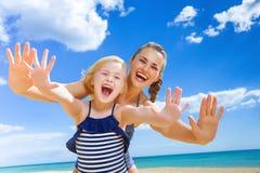 快乐的年轻母亲和孩子有的海滨的乐趣时间 库存图片