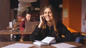 快乐的年轻美丽的妇女坐在咖啡馆和谈话在电话 股票视频