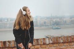 快乐的微笑的十几岁的女孩喜欢听到音乐 免版税库存图片