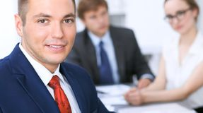 快乐的微笑的商人画象反对一个小组的商人在会议上 库存图片