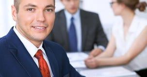 快乐的微笑的商人画象反对一个小组的商人在会议上 免版税库存图片