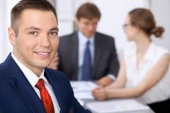 快乐的微笑的商人画象反对一个小组的商人在会议上 免版税库存照片