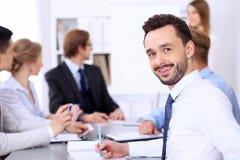快乐的微笑的商人画象反对一群人的在会议上 免版税库存图片