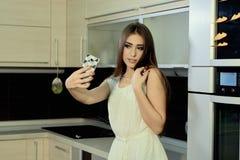 快乐的微笑的年轻白色皮肤女性与摆在厨房的长的深色的头发,在智能手机做selfie 免版税库存图片