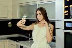 快乐的微笑的年轻白色皮肤女性与摆在厨房的长的深色的头发,在智能手机做selfie 库存图片
