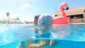快乐的微笑的母亲慢动作水下的录影有儿子游泳的在水池热的晴天 股票视频