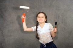 快乐的微笑的年轻小女孩孩子在背景墙壁的颜色画进行创造性的修理 图库摄影
