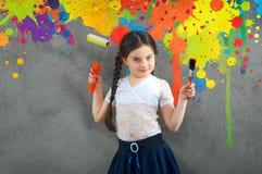快乐的微笑的年轻小女孩孩子在背景墙壁色的油漆画进行创造性的修理 免版税库存照片