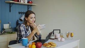 快乐的微笑的woamn在家谈网上录影闲谈使用智能手机在厨房里 库存图片