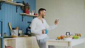 快乐的愉快的人跳舞和唱歌在厨房里,当在家冲浪在他的智能手机的社会媒介早晨时 免版税库存照片