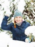 快乐的愉快的俏丽的女孩在冬天森林里演奏雪球 免版税库存图片