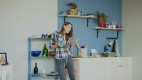 快乐的愉快的女孩跳舞和唱歌在厨房里,当在家冲浪在她的智能手机的社会媒介早晨时