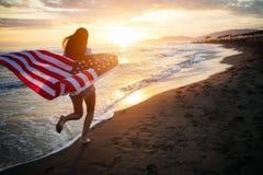 快乐的愉快的妇女户外在拿着美国旗子的海滩获得乐趣 免版税库存图片