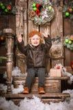 快乐的愉快的矮小的两岁的男孩在braun皮夹克、裤子和起动穿戴了与试验帽子在摆在圣诞节deco 免版税库存图片