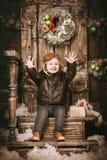 快乐的愉快的矮小的两岁的男孩在braun皮夹克、裤子和起动穿戴了与试验帽子在摆在圣诞节deco 库存图片