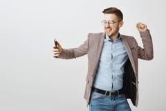 快乐的愉快的英俊的欧洲男性企业家室内射击时髦夹克的在蓝色衬衣跳舞无忧无虑 免版税库存照片