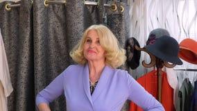 快乐的成熟妇女在尝试新的礼服的试衣间在时尚陈列室 选择时髦的礼服的微笑的资深妇女 股票视频