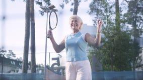快乐的成熟妇女在网球赛中获胜 跳跃的老妇人举手与在赢得的球拍 股票录像