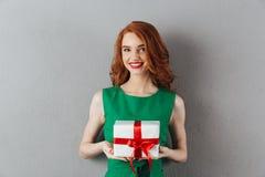 快乐的拿着礼物的绿色礼服的红头发人少妇 库存图片