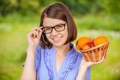 年轻快乐的拿着篮子用果子的妇女佩带的玻璃 免版税库存照片