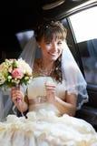 快乐的新娘到大型高级轿车里 库存图片
