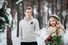 快乐的新娘和新郎在灰棕色被编织的套头衫在多雪的森林选择聚焦走在新郎 附庸风雅 免版税图库摄影