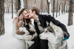 快乐的新婚佳偶在爱斯基摩背景亲吻  户外婚姻冬天的新娘新郎 附庸风雅 免版税库存图片