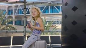快乐的旅客藏品护照和机票,当坐手提箱在机场时 影视素材