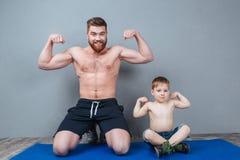 快乐的显示二头肌的父亲和他的小儿子 库存图片