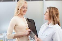 快乐的普通开业医生与患者一起使用 免版税库存照片