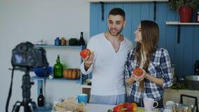 快乐的有吸引力的关于在家烹调的夫妇录音录影食物博克在dslr照相机在厨房里 库存照片