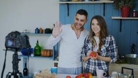 快乐的有吸引力的关于在家烹调的夫妇录音录影食物博克在dslr照相机在厨房里 库存图片